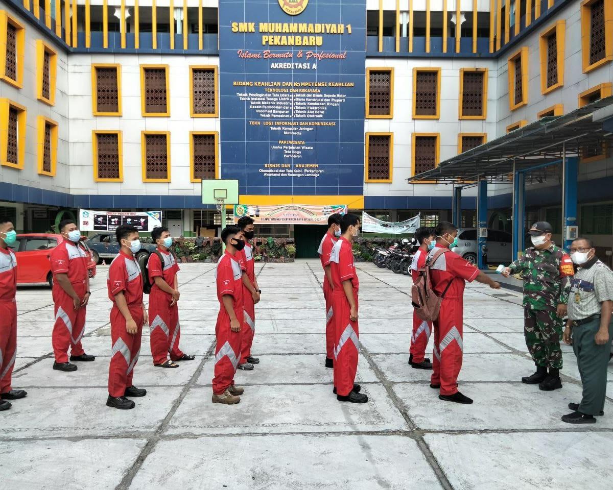 Babinsa Kodim 0301/PBR Lakukan Sosialisasi dan Monitor Prokes Serta Bagikan Masker Kepada Siswa SMK Muhammadiyah 1 Pekanbaru